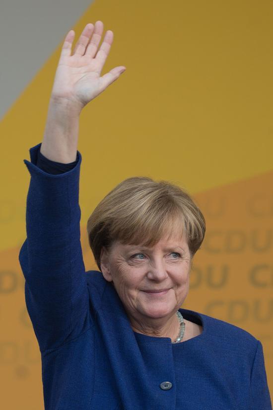 9月21日,在德国弗里茨拉尔,德国总理、基督教民主联盟(基民盟)主席默克尔在竞选集会上向人们挥手致意。  新华社 图