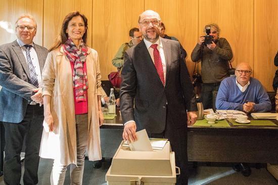 9月24日,在德国西部的维尔瑟伦,德国社会民主党主席、总理候选人舒尔茨(前右)在位于市政厅的投票站参加联邦议院选举投票。  新华社 图