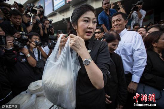 当地时间2016年11月11日,泰国曼谷,因米价下跌农民大受打击,泰国前总理英拉现身街头亲自帮助米农卖大米,声援米农。图片来源:视觉中国