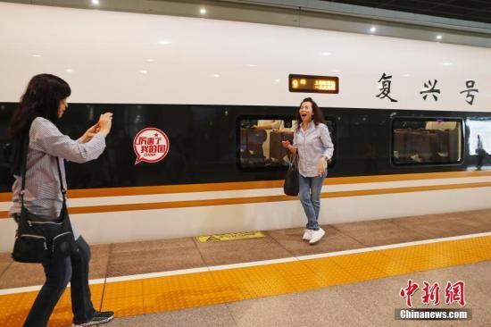 """旅客在铁路上海虹桥站与""""复兴号""""列车合影留念(资料图)。殷立勤 摄"""
