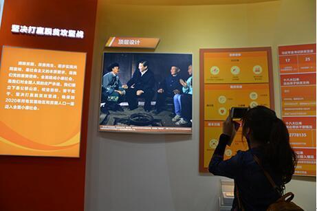 观光群众用手机记载着脱贫开发取得的成就。(人民网记者李彤摄)