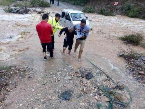 图为民警跳入湍急的河流中,抢救被困人员及车辆。