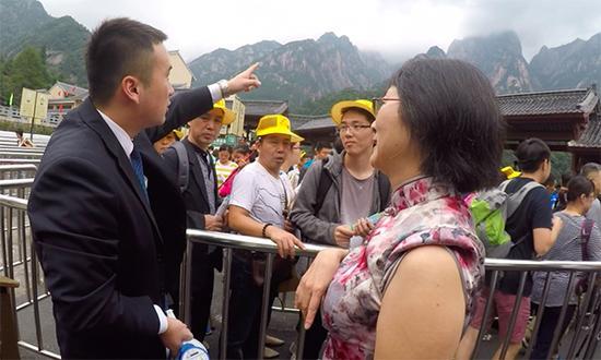 张仕庆耐心解答游客的疑问。澎湃新闻记者 胡芮默 图