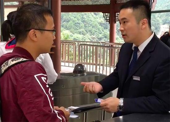 张仕庆在检票口向游客解释门票优惠政策。澎湃新闻记者 胡芮默 图