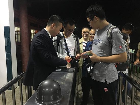 10月2日凌晨5:23,张仕庆在检票口为当天第一批赶上山的游客检票。澎湃新闻记者 胡芮默 图