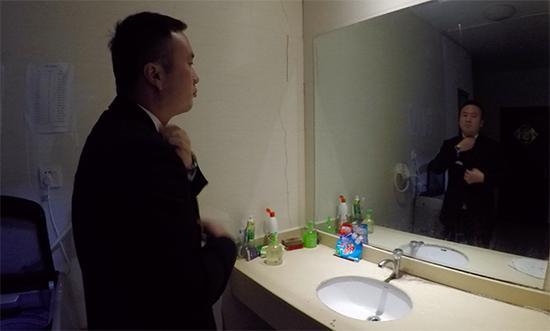 上岗前,张仕庆对着镜子整理领带。澎湃新闻记者 胡芮默 图