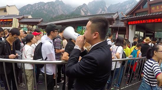 张仕庆拿起喇叭走向游客排队区。澎湃新闻记者 胡芮默 图