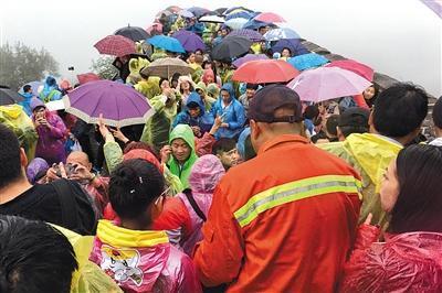 10月2日,八达岭长城景区,保洁工作人员穿过人流清理景区垃圾。因为游客暴增,工作人员巡视的速度变得慢了许多。本版摄影/新京报记者 王嘉宁 摄