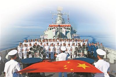 该支队官兵在大洋上面对国旗高唱军歌。王 栋摄