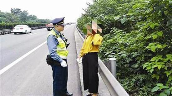 """民警拦下在应急车道上行走的女子。 """"成都交通运输""""微博 图"""