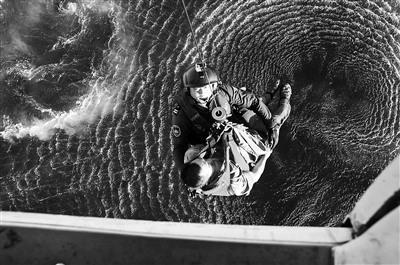 救援人员通过索降的方式将中毒渔民吊到直升机里