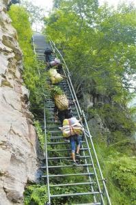 """9月22日,沼觉县支尔莫乡阿土列尔村勒尔组,当地村民组成的""""背夫队""""爬钢梯运物资。"""