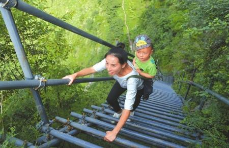 ①9月26日,沼觉县支尔莫乡阿土列尔村勒尔组幼教点的吉伍尔洛老师背着孩子爬钢梯。在以前没有钢梯时,她从山下到山顶要6个小时,如今只需要2个小时左右。