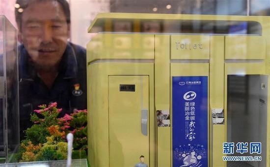 云南冶金昆明重工有限公司首席技师耿家盛在他带队研发的生态环保厕所的模型前(9月22日摄)。新华社记者 蔺以光 摄