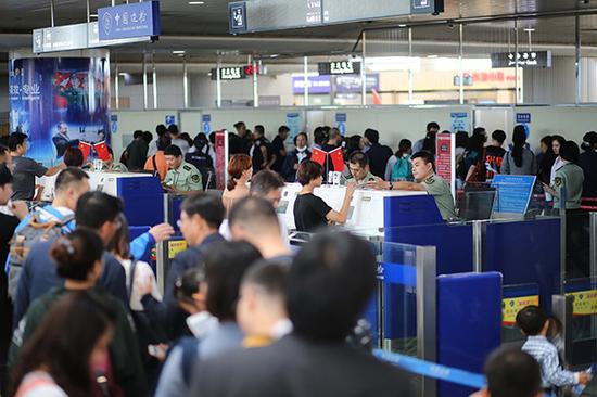 2017年9月30日,山东青岛。青岛机场边检站民警为出境游旅客办理通关手续。视觉中国 图