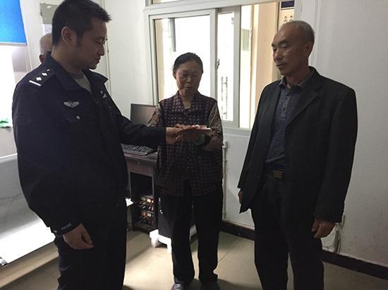 杨开科(右一)将黑包交还给蒙高松的妹妹。安岳县公安局 供图