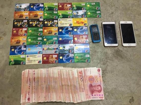 警方收缴的诈骗团伙作案用的手机银行卡以及查获的涉案现金