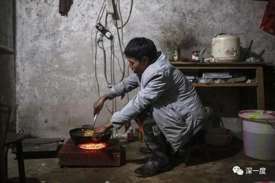 △天黑后,郭普全在用电炉炒菜,身后的电饭锅里正煮着米饭。