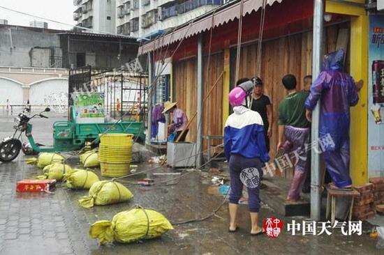 15日白昼,广东湛江风雨逐步显着,市民正在加固门窗。(图/殷美祥)