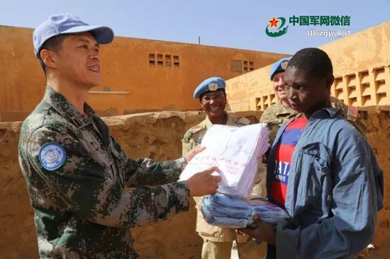 """警卫分队副队长向孩子们捐赠印有中英文""""中马友谊世代长存""""的T恤衫。 韩立建 摄"""