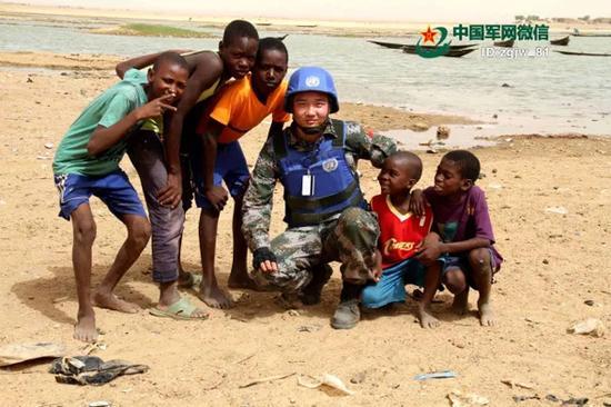 2015年7月1日,作者在尼日尔河畔与当地儿童合影。 中国军网 资料图