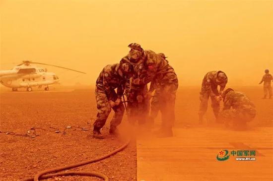 中国赴马里维和部队官兵在沙尘暴中紧急展开加奥机场直升机停机坪建设任务。 中国军网 资料图