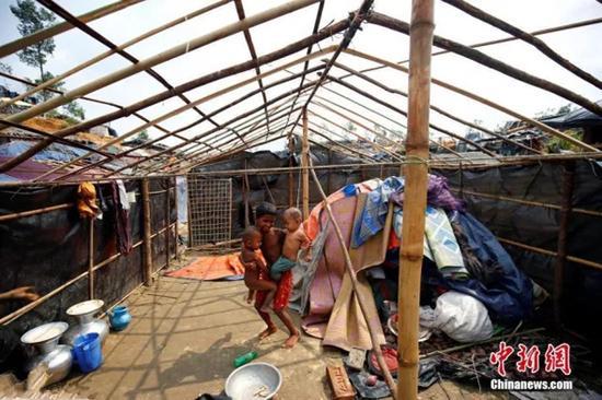 一个小罗兴亚难民抱着两个更小的孩子在被风暴摧毁的房屋里。 中国新闻网 资料图