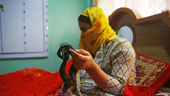 一名妇女展示被剪的头发。(图/印度斯坦时报)