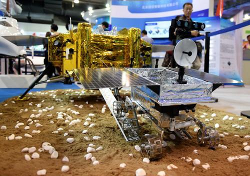 """资料图片:2016年5月19日,观众在科博会上参观""""玉兔号""""月球车模型。新华社记者 张晨霖 摄"""
