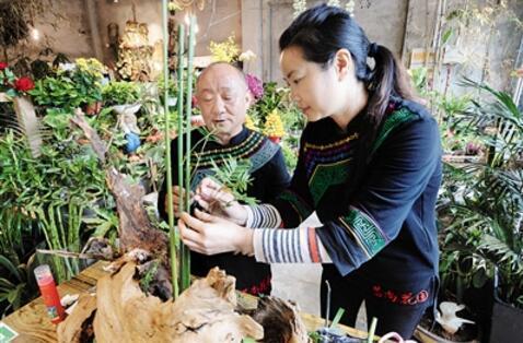 张云贵和弟子汪思言在创作花艺作品。