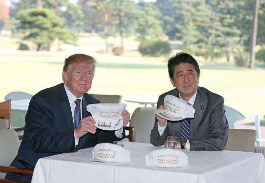 """特朗普和安倍晋三在印有""""Make alliance even greater""""(译为""""让美日同盟更伟大"""")字样的帽子上签名。"""