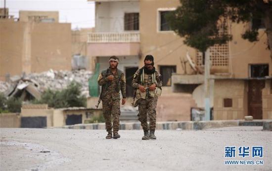 """资料图:在叙利亚拉卡附近的塔卜卡镇,两名""""叙利亚民主军""""士兵走在街道上。"""
