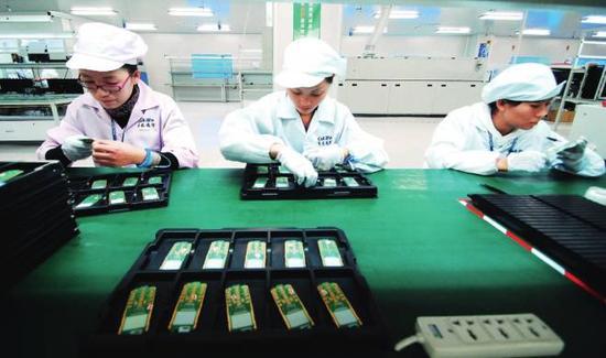 2010年11月,江西省九江市共青城工业园区,赛龙通信公司的工作人员在进行手机芯片生产作业。图/视觉中国
