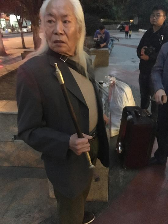 在成都自家小区门口逗留的黄云彪,当晚他没有回家,在两名男子陪同下入住附近一家宾馆。澎湃新闻记者 王万春 图