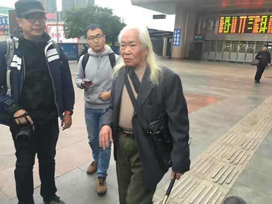 黄云彪手持烟枪,他称宝剑已送给了王鸿达,图为媒体记者们试图采访黄云彪。澎湃新闻记者 王万春 图