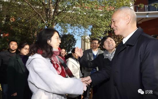 与青年教师握手