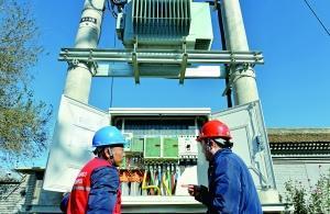 """昨天,北京电力公司的工作人员在实施了""""煤改电""""的顺义区东水泉村使用红外设备对电路进行检测,保障村民安全采暖。北京晨报记者 李木易/摄"""