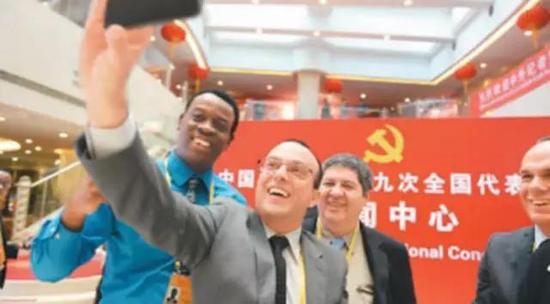 外国记者在十九大新闻中心拍照留影。胡庆明摄(人民视觉)