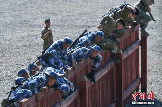 资料图为中俄双方海军陆战队员翻越围墙障碍。中新社记者 任东 摄
