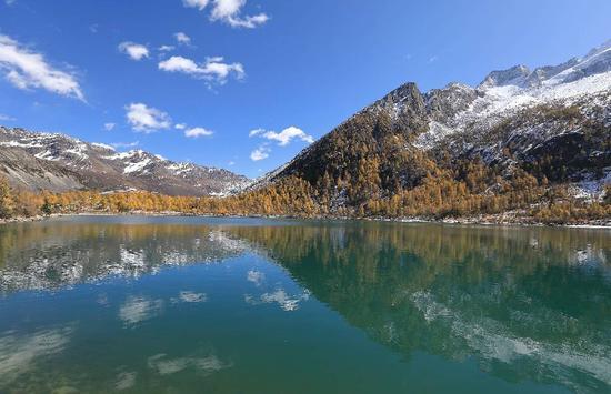 ▲四川雅拉雪山下,蓝天、白云、彩林和碧绿的湖水组成一幅漂亮画卷。 图/新华社