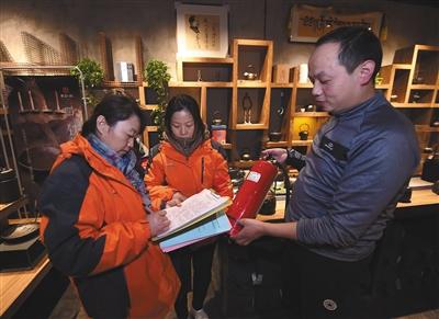11月19日,向阳区高碑店村村委会事情职员检查辖区内一家商铺的消防设施。 新华社记者 罗晓光 摄