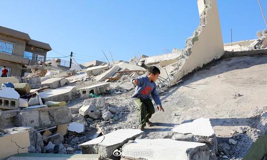 伊朗克尔曼沙省阿兹格雷市附近,一个孩子在地震废墟上玩耍 图据《卫报》