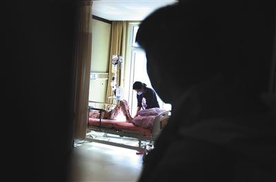 11月16日,燕郊燕达陆道培医院,因为肠道排异反应,10岁的白血病患者萱萱(化名)躺在病床上输液,其母亲在一旁照顾,父亲则透过门缝看孩子一眼。A08-A09版摄影/新京报记者 大路