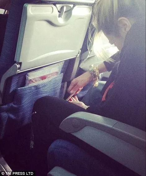 ▲小姑娘用修脚锉锉着她的红色脚趾甲,其他乘客表示hǐn无奈。