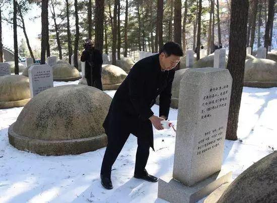 △宋涛在一尊烈士墓前躬身祭酒