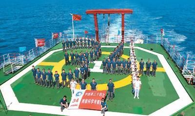 """11月15日,中国第34次南极科学考察队在""""雪龙""""号停机坪组成""""34""""字样的队形合影留念。"""