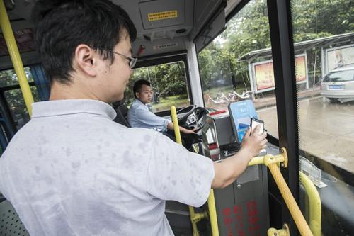 资料图片:6月15日,一名搭客在湖北武汉用手机刷支付宝搭乘公交车。新华社记者 肖艺九 摄
