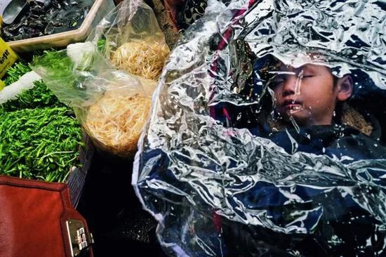 在纽约唐人街,你能买到最新鲜的鱼、肉和蔬菜,也能吃到最正宗的中国菜,图中,菜市场的孩子在菜摊旁熟睡。