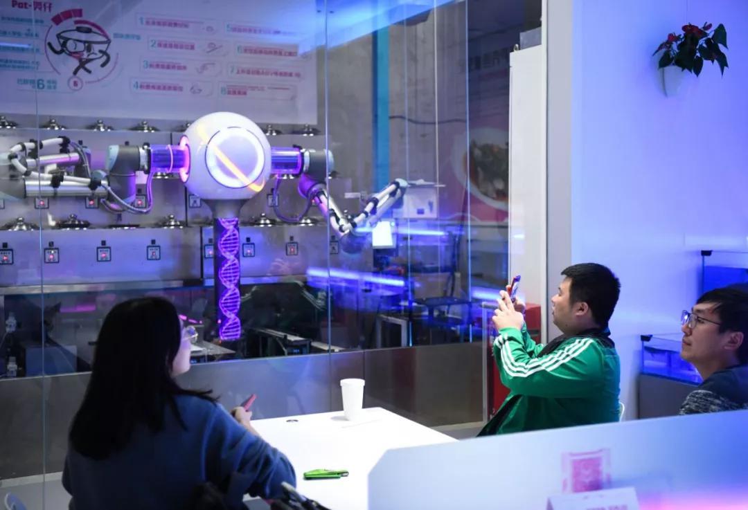 ▲顾客在观看煲仔饭机器人操作。(新华社)