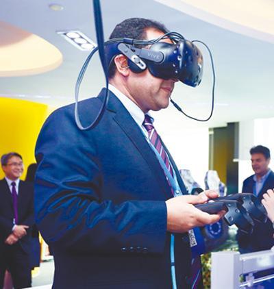 与会代表参观广州一家高科技企业并体验其生产的虚拟现实设备。资料图片